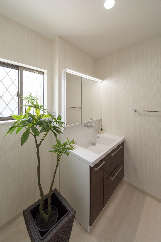 白を基調とした清潔感のあるサニタリールーム。木目調ブラウンの洗面化粧台がナチュラルな雰囲気を演出。