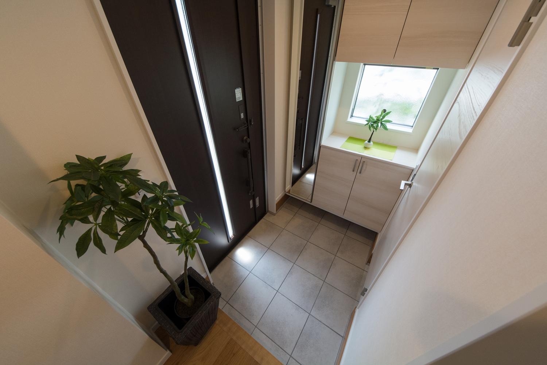 玄関ドアの縦スリットと小窓から自然の光が差し込み、明るく開放感があります。