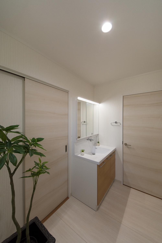 白を基調とした清潔感のあるサニタリールーム。木目柄の洗面化粧台がナチュラルな雰囲気を演出。