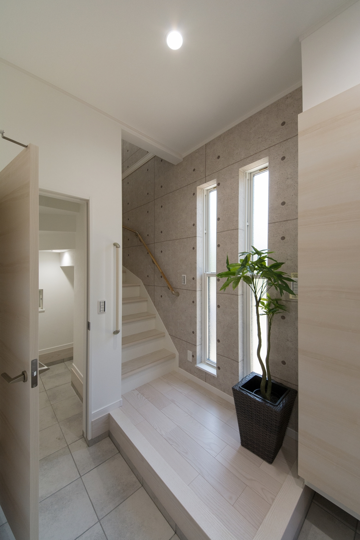 子世帯専用玄関ホール。白い空間に、コンクリート調クロスが印象的でギャラリーの様な空間。