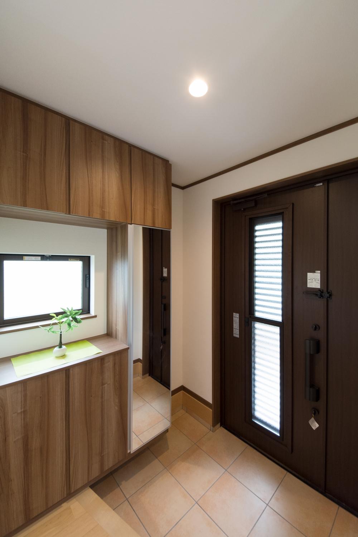 玄関ドアのガラス部分と、建具の窓から差し込む光と風が、明るく開放的ある空間に