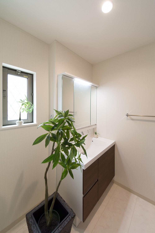 白を基調とした清潔感のあるサニタリールーム。モカ色の洗面化粧台扉がナチュラルな雰囲気を演出します。