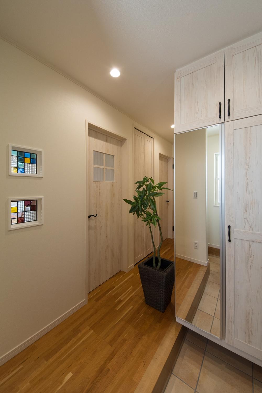 目を惹く色鮮やかなステンドグラス。玄関収納扉も室内のドアとお揃いのデザインに。