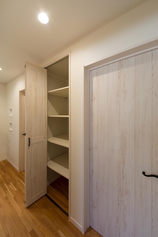 廊下の収納スペース。入れたい物の高さに合わせられる可動タイプの棚。