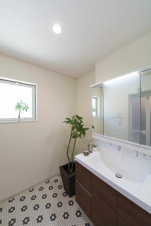 愛らしい花柄のフロアが印象的なサニタリールーム。洗面台はワイドなタイプで広々とお使いいただけます。