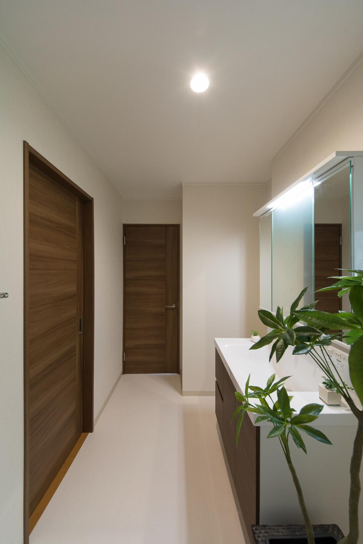 白を基調とした清潔感のあるサニタリールーム。洗面化粧台はモカカラーで建具との統一感を。