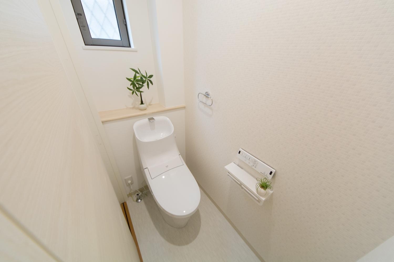 1階トイレ。タイル調のアクセントクロスがオシャレな空間を演出。