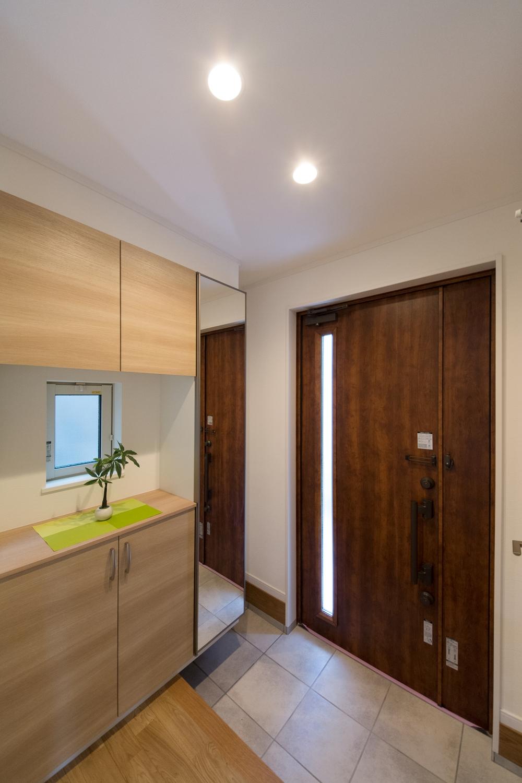 木目調ブラウンの玄関ドアとベージュのテラコッタ調タイルがナチュラルな雰囲気を演出。
