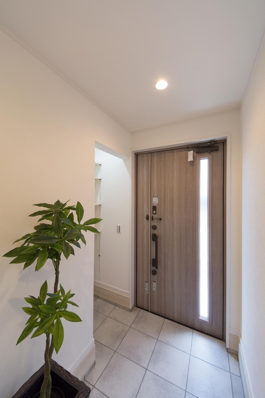 アッシュ系の色味の玄関扉がスタイリッシュな印象に。収納に便利なシューズクロークを設えました。
