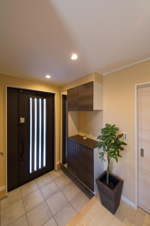 小世帯玄関/ダウンライトの色味と木目調の収納が温かみのある空間を演出。