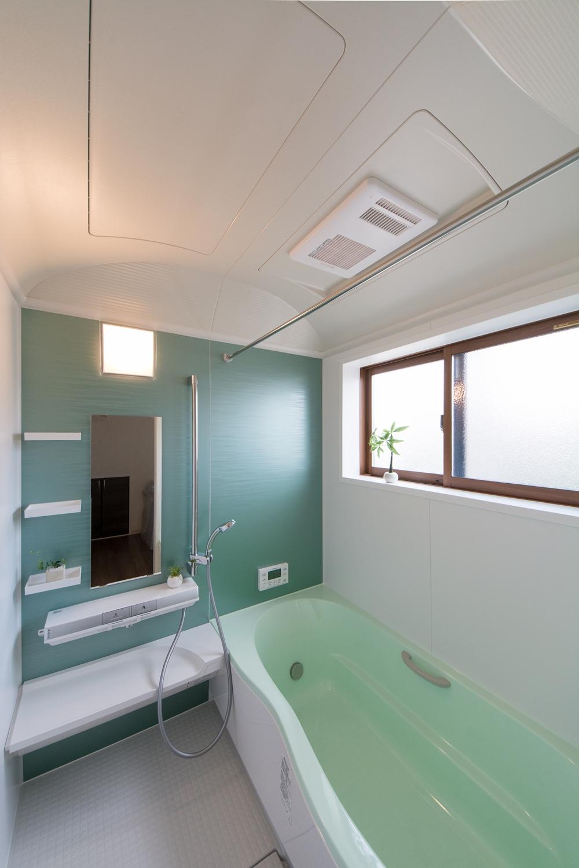 子世帯バスルーム/グリーンのアクセントパネルと浴槽が爽やか&リラックス空間を演出。