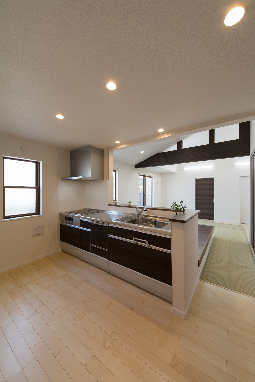 広々としたキッチンスペース。扉カラーは木目調のダークブランで落ち着いた印象に。