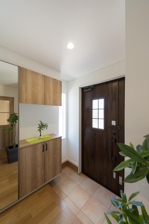 アンティーク調の玄関扉とベージュのテラコッタ調タイルがナチュラルな雰囲気を演出。