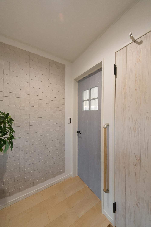 エージング加工されたブルーペイントのドアと空気を美しく整えるインテリア壁材「エコカラット」が空間を彩ります。
