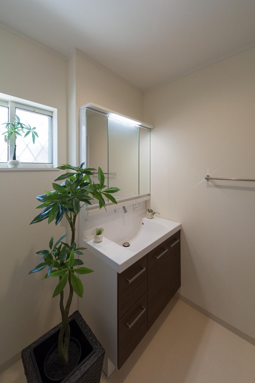 白を基調とした清潔感のあるサニタリールーム。モカの洗面化粧台がナチュラルな雰囲気を演出。