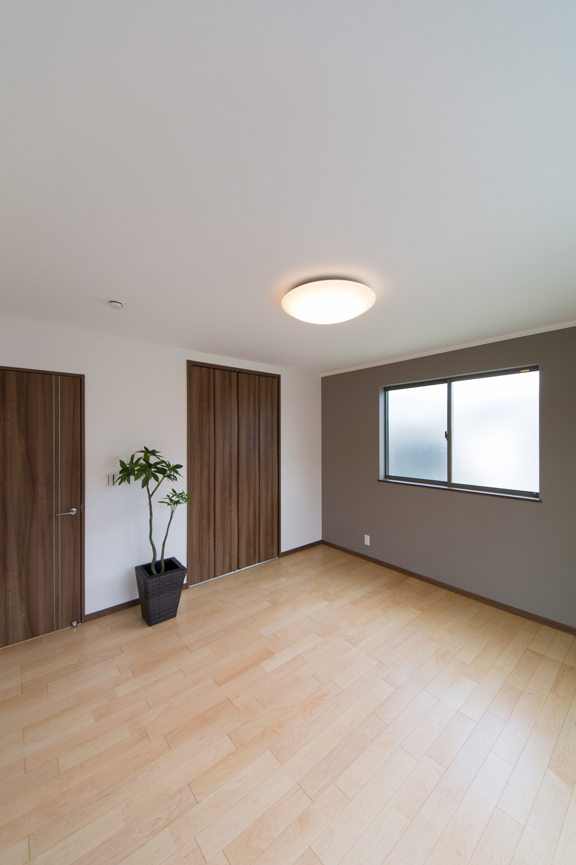 2階洋室/ベージュのアクセントクロスが空間を引き締め、モダンな雰囲気を演出。