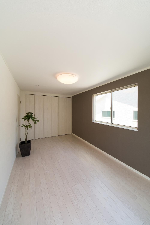 グレーのアクセントクロスが空間を引き締め、モダンな雰囲気を演出。家具とのコーディネートも楽しめます。