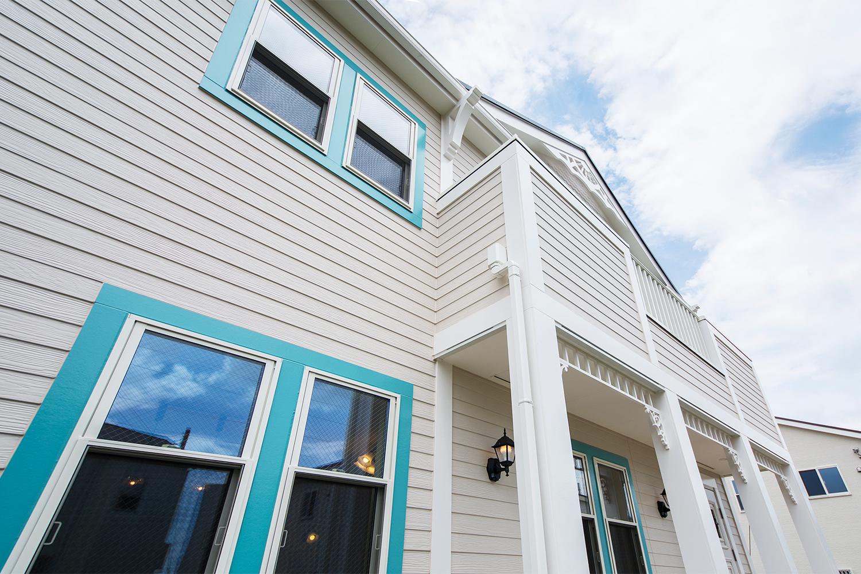 白に近い木目調のベージュを基調にブルーグリーンの窓モールをアクセントにした、コンテンポラリースタイル住宅。