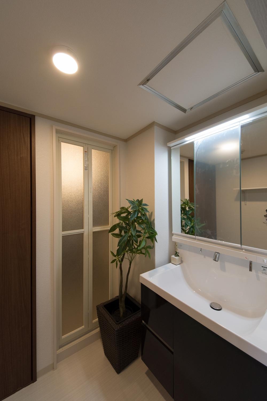 白を基調とした清潔感のあるサニタリールーム。ディープグレーの洗面化粧台がシックで落ち着いた雰囲気を演出。