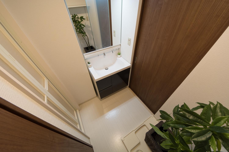 白を基調とした清潔感のあるサニタリールーム。建具もナチュラルな木目調に変えました。