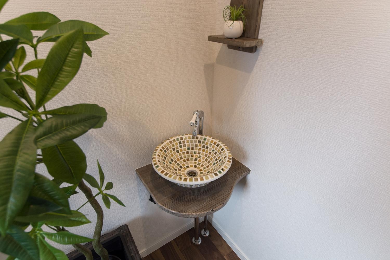 カラフルでアンティークなモザイクタイルの手洗いがお客様をお迎えします。木製の棚がさりげなくて素敵。