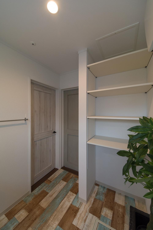古びた感が素敵なエイジングペイント調のフロア。タオルや洗剤等をたっぷり収納できるリネン棚を設置。