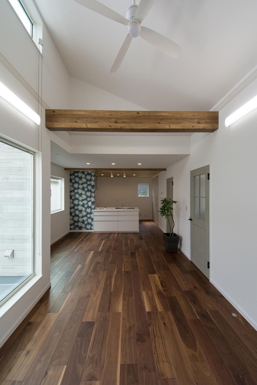 2階LDK/キッチンと壁の白をベースに、フローリングと化粧梁の深い色味がメリハリを与えています。建具や花柄クロスがポイントになってハイセンスな空間に。