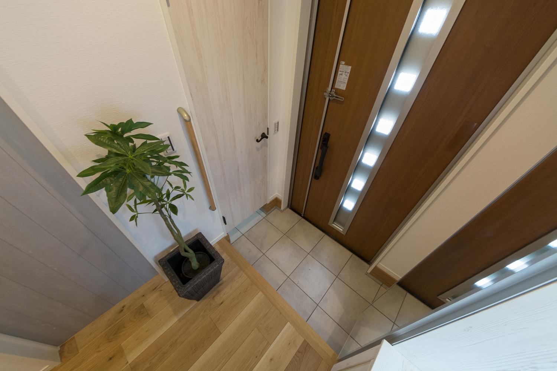 ナチュラルな雰囲気を演出するブラウンの玄関ドア。小窓部分から差し込む光が、明るく開放的ある空間を演出。