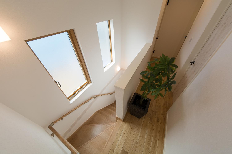 2つの窓からの穏やかな光が降り注ぐ開放感のある階段。