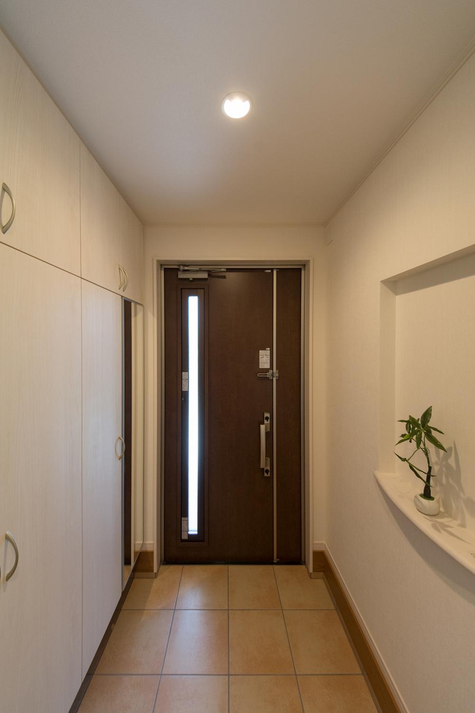 ブラウンの玄関扉とベージュのテラコッタ調タイルがナチュラルな雰囲気を演出。