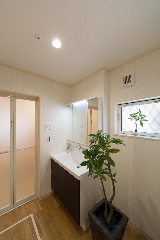 白を基調とした清潔感のあるサニタリールーム。ダークブラウンの洗面化粧台とフローリングナチュラルな雰囲気を演出。