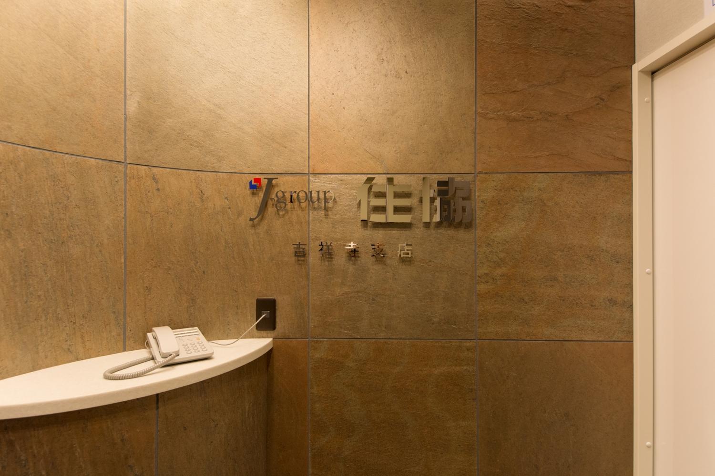 間接照明と石材を使用した壁が空間を彩る、シックで高級感のあるエントランス。