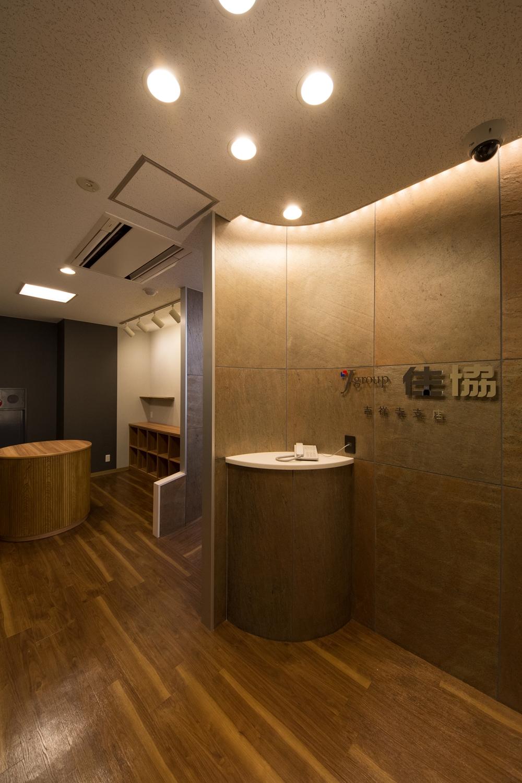 石材を使用した壁と間接照明が空間を彩る、シックで高級感のあるエントランス。