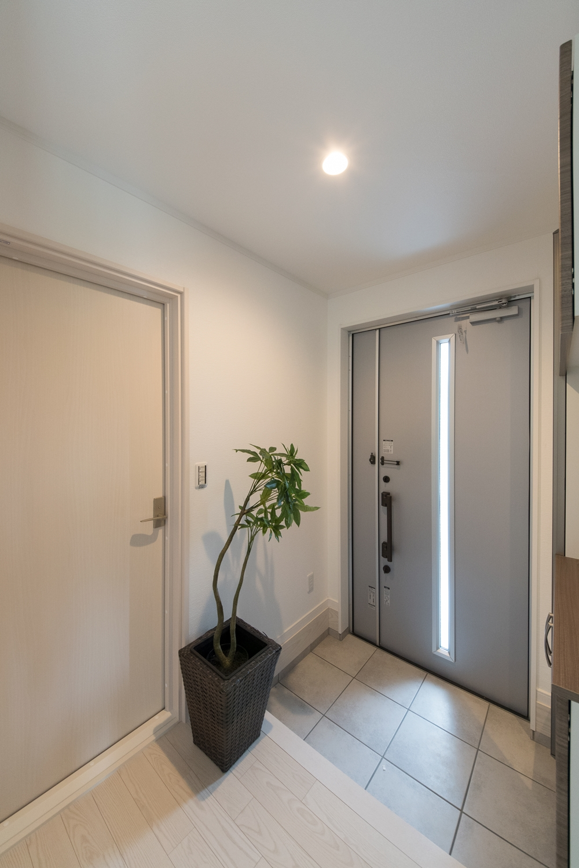 縦スリットから光が差し込むシルバーのドア。爽やかでスッキリとした印象の玄関に。
