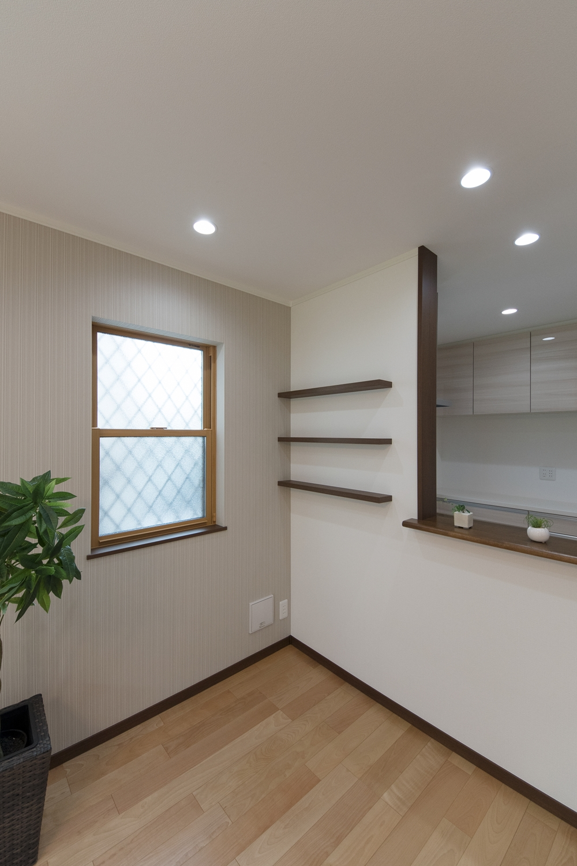 キッチンの壁に、小物のディスプレイを楽しめる固定棚を設え、窓側の壁は、ベージュのクロスでアクセントにしました。