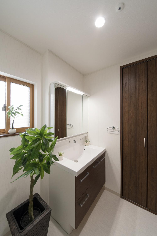 清潔感のあるサニタリールーム。木目調の洗面化粧台がナチュラルな雰囲気を演出。