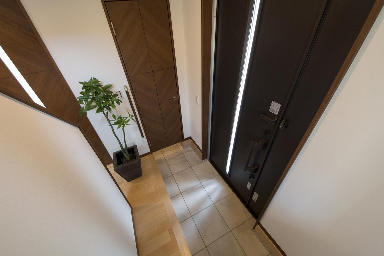 ドアの縦スリットから自然の光が差し込む明るい玄関。シューズクロークを備え収納たっぷり。