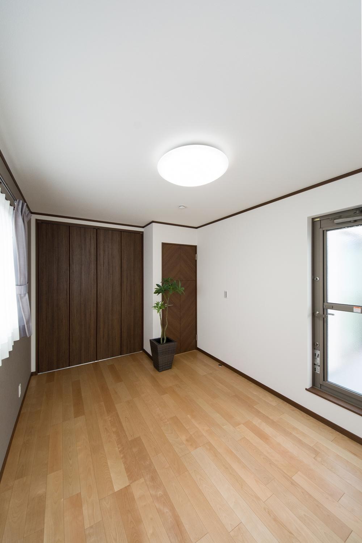 2F洋室/穏やかな木目のバーチを床材にダークブラウンの建具を合わせ、落ち着いた印象に。