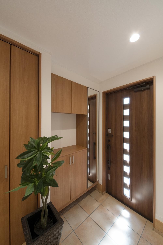 ドアの小窓から自然の光が差し込む明るい玄関。テラコッタ調タイルがナチュラルな雰囲気に。