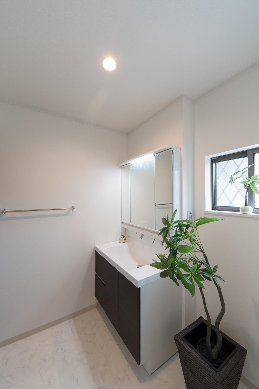 白を基調とした清潔感のあるサニタリールーム。扉カラーをダークブラウンでアクセントにしました。