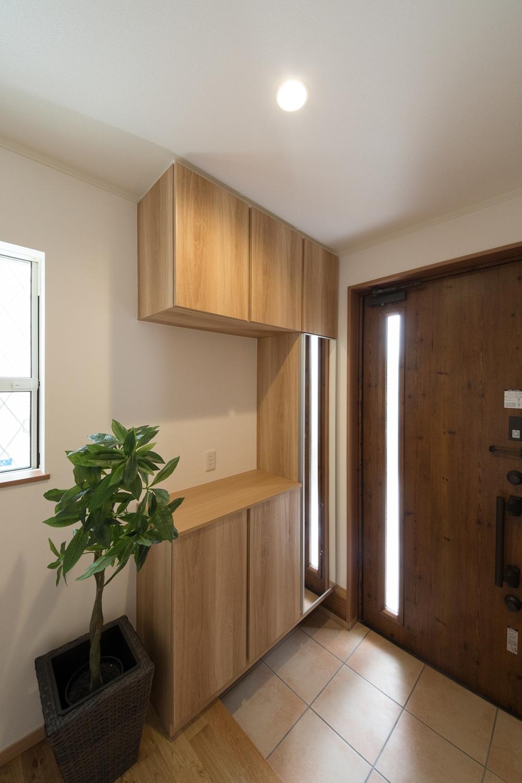 木目調の玄関扉とベージュのテラコッタ調タイルがナチュラルな雰囲気を演出。