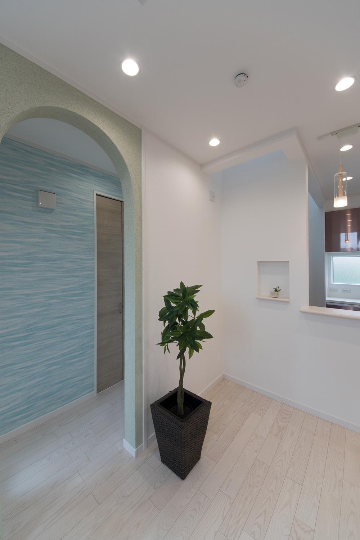 リビング入口のアーチ型の下がり壁。ザラッとした自然の素材感や光の陰影を楽しめる塗り壁でできています。