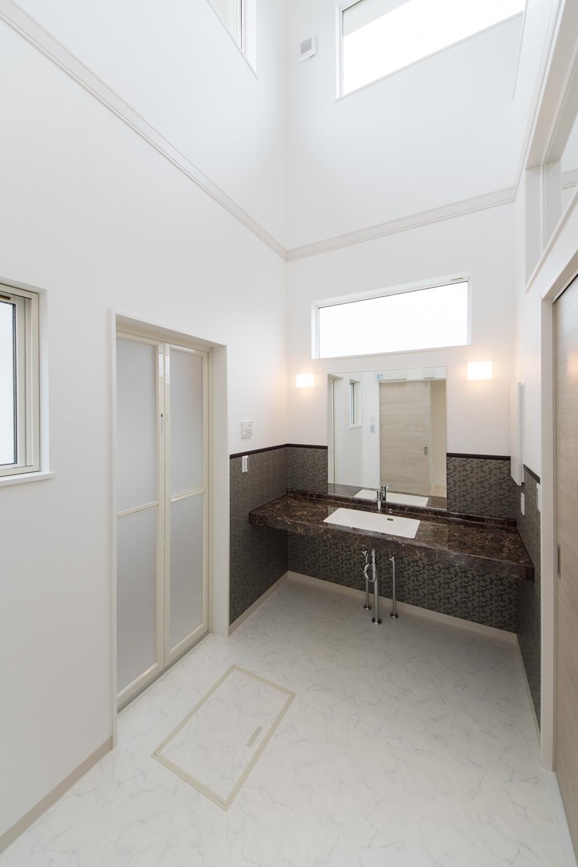 吹抜け空間のサニタリールーム。美しさと機能性を併せ持つ洗面カウンターは、人工大理石でできています。