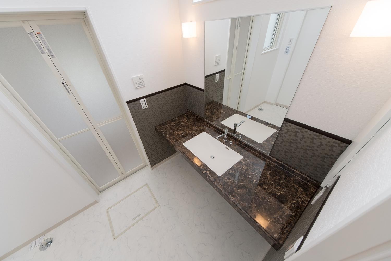 広々としたサニタリールーム。美しさと機能性を併せ持つ、人工大理石の洗面カウンター。