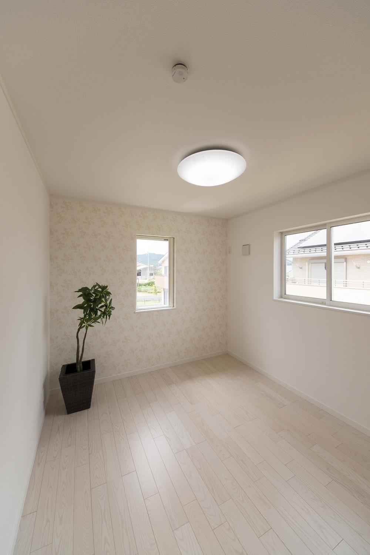 2階洋室/花の柄をモチーフにした白のアクセントクロスがエレガントな空間を演出。