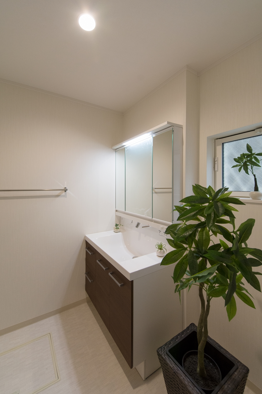 白を基調とした清潔感のあるサニタリールーム。モカ色の洗面化粧台がナチュラルな印象に。