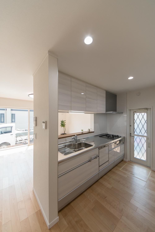 爽やかな白い木目調のキッチン扉。清潔感溢れるキッチンスペース。