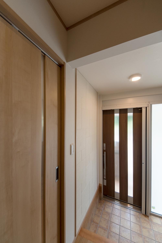 開き戸だった玄関ドアを、開け閉め簡単な引き戸にし、タイルも貼り替えました。