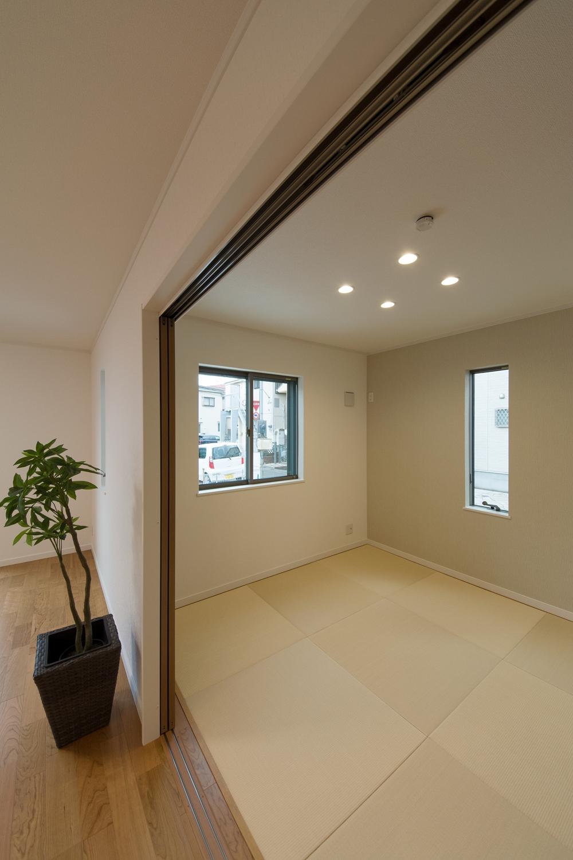 アイボリーのアクセントクロスと縁なし畳の優しい色使い。モダンな空間の1F畳敷き洋室。