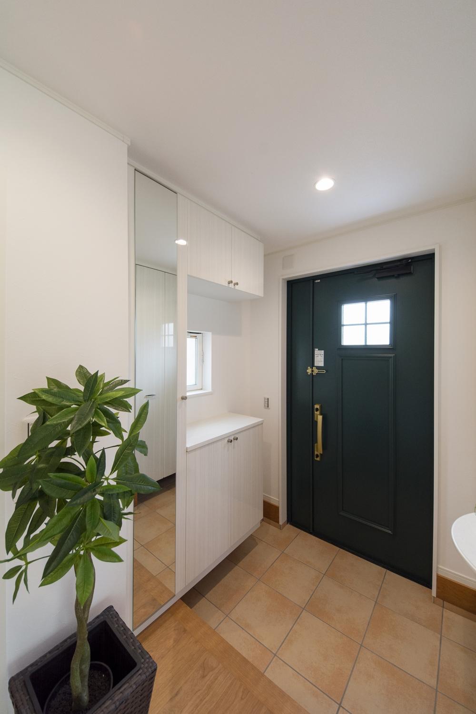 上品さと個性を持った玄関。扉は、木目調ペイント仕上げの深みあるグリーンにゴールドのハンドルを施しました。